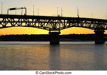 A silhouetted bridge at sunset on t