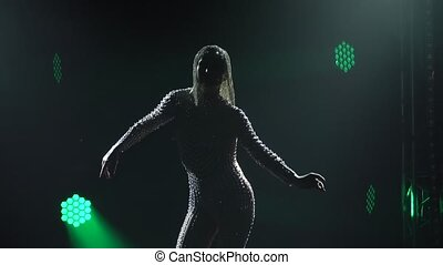 A silhouetted dancer in a shiny costume decorated with stones and rhinestones and chic headdress dances passionately on stage in the center of green attention. Close up in slow motion