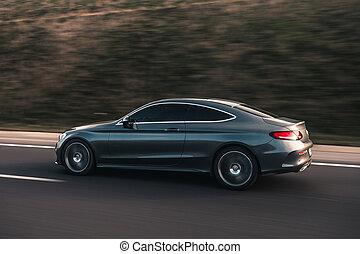 A silver luxury sedan on the road