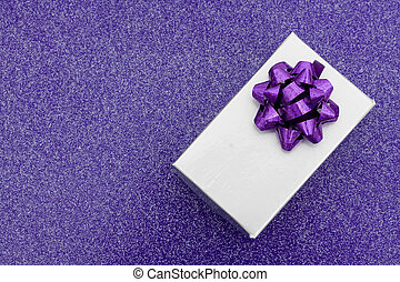 A silver present with bow on purple background