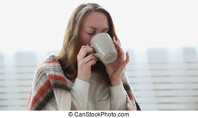 a simple woman drinks tea wrapped in a warm woolen blanket