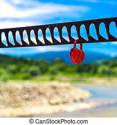 a, singel, hjärta gestaltade, röd, hänglås, symbolizing, kärlek, hängande, den, bro, ledstänger, med, suddig, flod, grönska, mountains, och blåa, sky, in, bakgrund