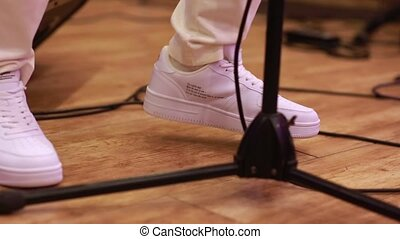 A singer man in white sneakers shoes knocks down the musical rhythm by dancing with his feet, while stands near microphone. Close-up side view hands shake camera shot.