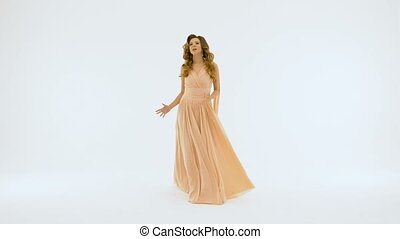 A singer with beautiful long hair, in a long beige dress singing against a white wall. Slow motion