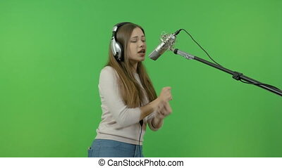 A singer with long hair sings into a studio microphone. On a green background.