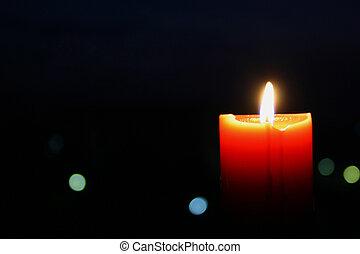 A single burning orange candle isolated