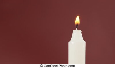 A Single Candle is Lit on a Red Background. White candle burning. Close-up. Place for titles. Seamlessly loop. Soft CandleLight. Isolated on red screen. Space reserved for captions. Macro. 4K 10 bit