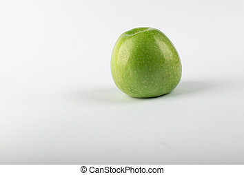 A single green fresh apple isolated on white background. side view