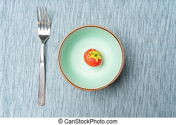 A single strawberry in a bowl as a symbol of a diet