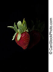 A single strawberry isolated on black