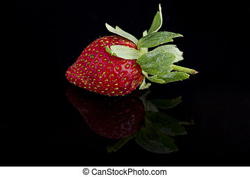 A single strawberry isolated on black background