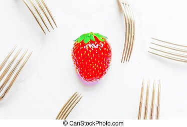 a single strawberry ,over saturated ,surrounded by silver vintage forks