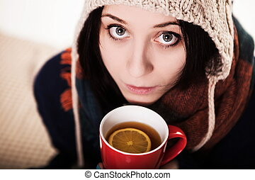 A sip of hot coffee in the winter. A girl in a knitted hat holdi