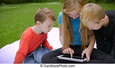 A sister shows her two younger brothers something on a tablet - slowmo handheld