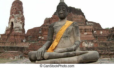 A wide, frontal shot of the Mara-posed sandstone image of Buddha at Wat Mahatthat, with the ancient red brick and stucco-finished Prang and Ubosot at the background.