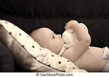 A six month old baby drinking out of his bottle