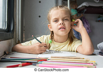 A six-year girl in the picture looked drawing pencils in a second-class train carriag