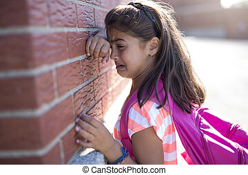 six years old school girl cry beside brick wall - A six...