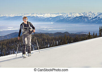 A skier walks in the winter mountains