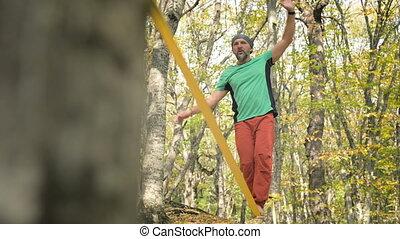 A Slack man aged with a beard in sportswear walks balancing ...