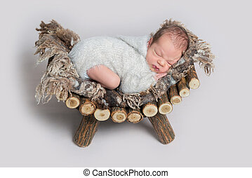 sleeping newborn boy on a wooden bed
