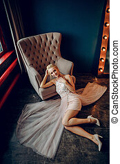 A slender blonde smiles and reclines on the black floor next to
