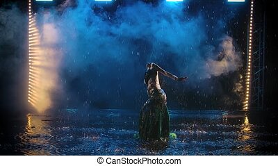 A slender long haired oriental dancer silhouetted against the background of smoke in the studio. A woman is dancing in the rain on the surface of the water. Slow motion
