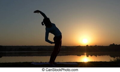 A slender woman bends aside at her mat at sunset - An...