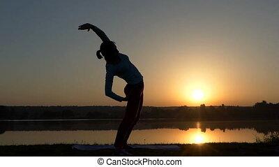 A slender woman bends aside at her mat at sunset - An...