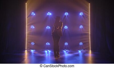 A slender woman in a suit and hat dances sexually in the ...