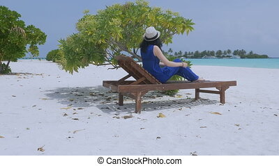 A slender young woman resting in a sun lounger on a tropical...