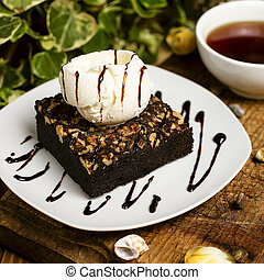 A slice of chocolate brownie with walnut and vanilla ice cream.