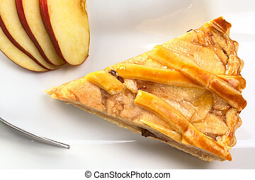 A slice of delicious apple pie with apple slices and fork photographed from above (Selective Focus, Focus on the top of the apple pie)