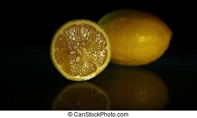 A slice of lemon and a whole lemon on a dark table. HD
