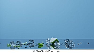 A slice of lime, ice and mint leaves on a glossy surface,...