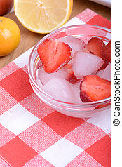 A slice of red strawberry on glass plate with lemon and mandarin in party theme background