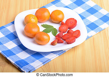 A slice of red strawberry on white plate with mandarin and strawberry slices