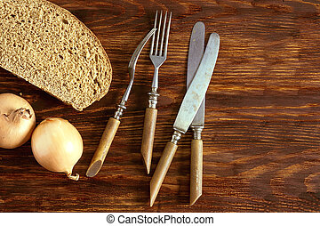 A slice of rye bread, onions and cutlery