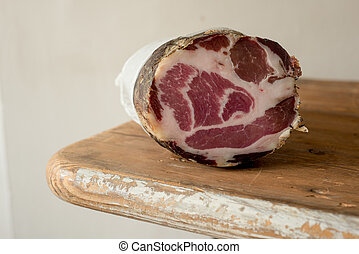 A Sliced Log of Coppa Meat - A sliced log of deli meat,...