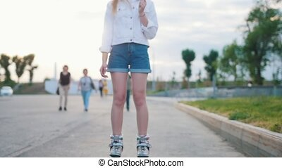 A slim smiling teenage girl in roller-skates skating in the...