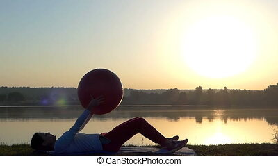 A slim woman lies on a mat with a fitball in hands at sunset