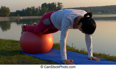 A slim woman rolls on a fitball with hands on her mat