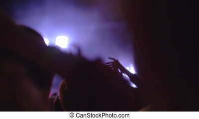 A slow motion of a crowd of fans at an evening music concert