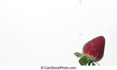 A slow motion of a strawberry being dropped in a clear water...