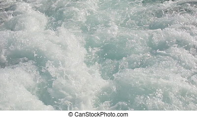 A slow motion view of the wake behind a sports boat at sea.