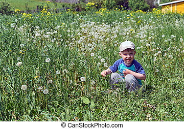 A small a boy sits in the grass, looks at us and smiles.
