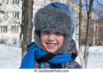 A small a boy winter sunlight a day to looks at us and smiles.