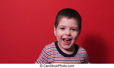 A small baby boy 3-4 years old laughs cheerfully on a red background in a striped bright T-shirt. Happy childhood and fun.