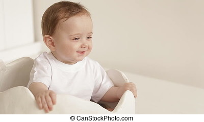 A small baby is sitting in a toy egg shell. little cute baby