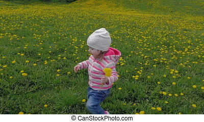 A small, beautiful girl runs around the city park. A child enjoys dandelions in the garden. Slow motion